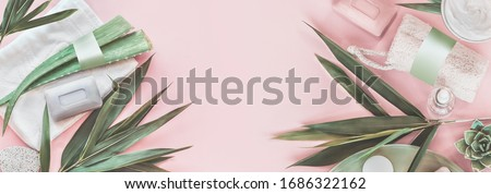 Modern skin care beauty and cosmetics concept with products bottles with mock up, aloe vera and palm leaves on pastel pink background. Natural cosmetic. Banner. Top view. Eco friendly. Zero waste. Royalty-Free Stock Photo #1686322162