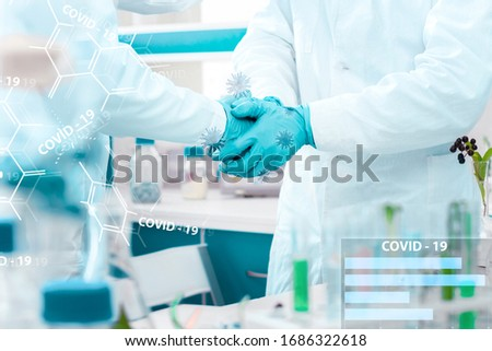 Closeup scientists handshake in medical gloves in laboratory. Pharmacists virologists invented vaccine against virus SARS-CoV-2, 2019-nCoV, Covid-19. Coronavirus pandemic epidemic concept. #1686322618