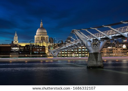 Blue hour over St Paul's Cathedral and Millenium Bridge with light trail over Thames river in London, England, United Kingdom (UK), a mix of ancient and modern architecture in one of the biggest city.
