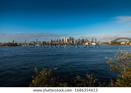 Sydney in Australia, taking pictures of the skyline seen from a park during a cloudy but warm day in summer.