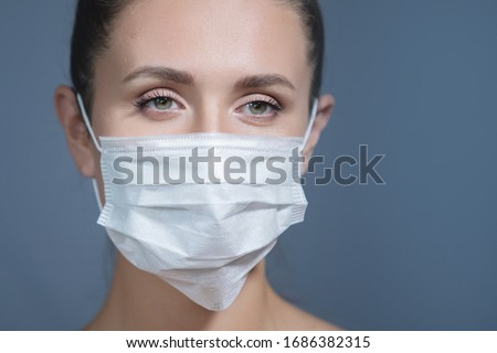 Young woman puts on a medical mask. Symptoms of influenza, fever, pandemic, epidemic. #1686382315