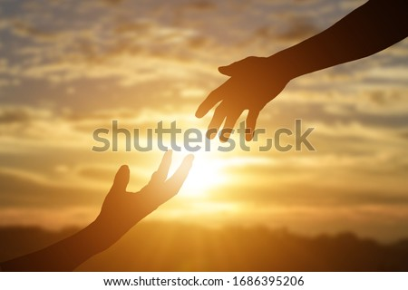Silhouette of reaching, giving a helping hand, hope and support each other over sunset background.  Royalty-Free Stock Photo #1686395206