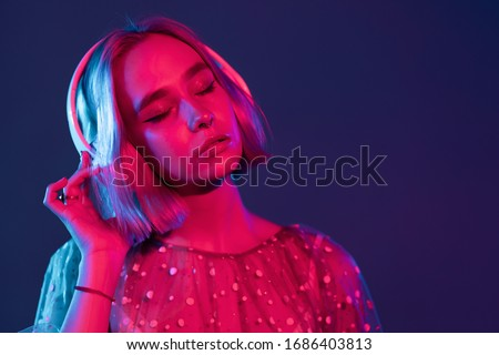 Mysterious hipster teenager listening to music with headphones. Portrait of millennial pretty girl with short hairstyle with neon light. Dyed blue and pink hair. #1686403813