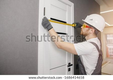 Carpenter worker installation process of measures cloth with ruler door hinge. #1686414658