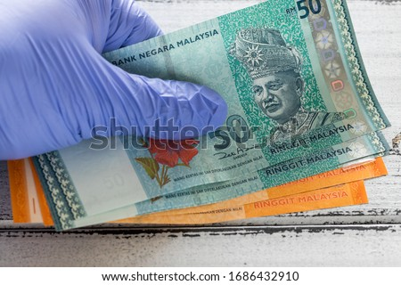 Malay money, ringgit banknotes kept in rubber gloves.  The concept of economy and financial threats during the Coronavirus pandemic Royalty-Free Stock Photo #1686432910