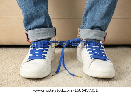 Man wearing sneakers with tied together laces, closeup. April fool's day Royalty-Free Stock Photo #1686439051
