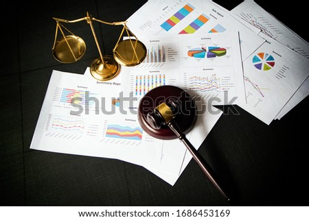Top view of  wooden judge gavel and Brass Scales put on business paper chart,black canvas background