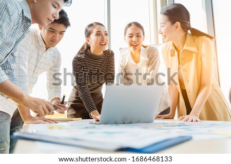 Group of asian young modern people in smart casual wear having a brainstorm meeting while sitting in office background. Business meeting, Planning, Strategy, New business development, Startup concept. #1686468133