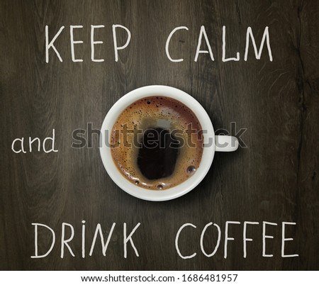 The cup of black coffee is on the wooden table with inscription keep calm and drink coffee.