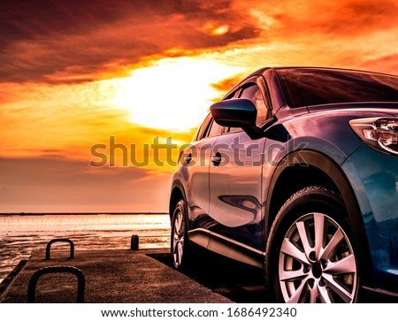 Blue luxury SUV car parked on concrete road by sea beach with beautiful red sunset sky. Summer vacation at tropical beach. Road trip. Front view sports and modern design SUV car. Summer travel by car. Royalty-Free Stock Photo #1686492340