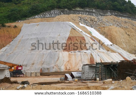 The geotextile fabric is spread over the surface of the slope to prevent erosion. Also to temporarily stabilize the slope before the permanent stabilization work done. #1686510388