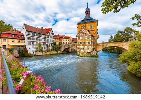 Bamberg city in Germany. Town hall building in background with blue cloudy sky.  Architecture and travel in Europe. Flowing river in foreground. #1686519142