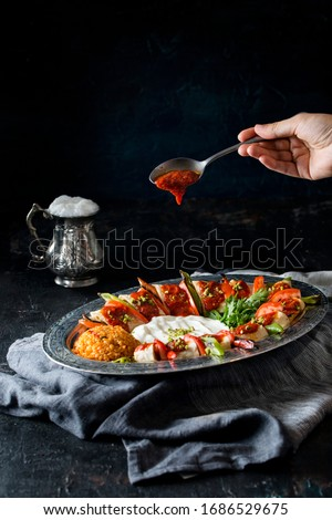 beyti turkish kebab, buttermilk and  sauce on the dark back ground #1686529675