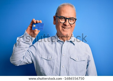 Middle age hoary man wearing glasses holding credit card as money to do payment with a happy face standing and smiling with a confident smile showing teeth