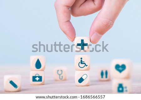 Hand chooses a emoticon icons healthcare medical symbol on wooden block , Healthcare and medical Insurance concept #1686566557