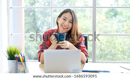 Social distancing, Work from home, Asian women working online with laptop computer at home office, Asia female smiling and holding coffee cup at home office, Happy girl study online class #1686593095