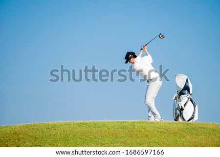 Asian man golfer standing  on slope  with golf bag hitting  golf ball on blue sky background  at golf course , Sport healthy holiday lifestyle  Concept #1686597166