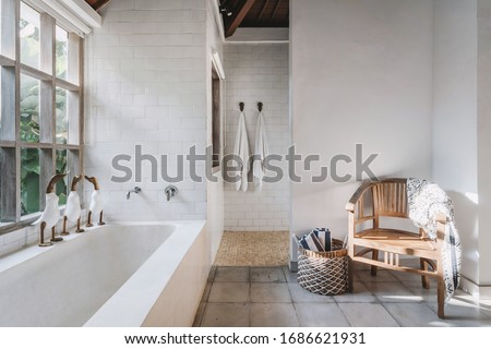 White and modern bathroom interior with chair, plaid, towels on hook and in basket, cute decor toys on built tub, large window in wooden frame with tropical foliage plants and copy space on wall #1686621931