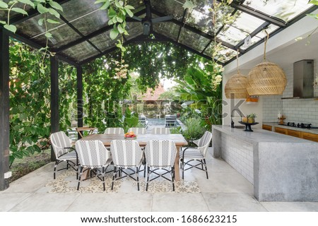 Open kitchen with empty dining room table and chairs outside, against green fresh plants on background Royalty-Free Stock Photo #1686623215