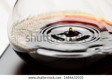 Brewing coffee with a filter dripper. Coffee dripping through a paper filter. Alternative way to make coffee. Macro close-up shot. Royalty-Free Stock Photo #1686632035