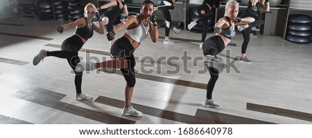 Women in black and white sportswear on a real group body Combat workout in the gym train to fight, kickboxing with a trainer Royalty-Free Stock Photo #1686640978