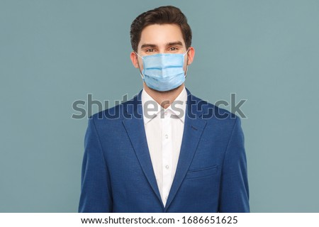 Portrait of handsome young businessman with surgical medical mask looking at camera. Business people medicine and health care concept. Indoor, studio shot on blue background #1686651625