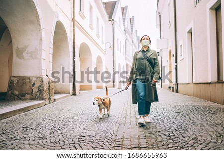 Young female fancy-dressed using a face mask as a coronavirus spreading prevention walking with her beagle dog on deserted old European squares and streets. Global COVID-19 pandemic concept image. #1686655963