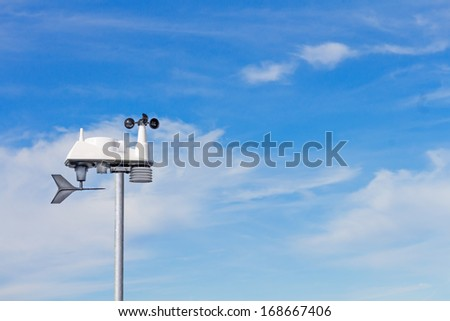 Modern wind speed and direction indicator. Wind vane, or weathervane, to show direction, and electronic anemometer with rotating cups to measure velocity. Blue sky and clouds background. Room for text #168667406