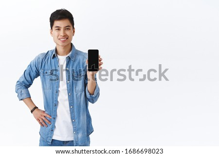 Technology, online lifestyle concept. Handsome smiling asian man introduce new application, recommend download app or use this messanger, showing mobile phone display, white background #1686698023