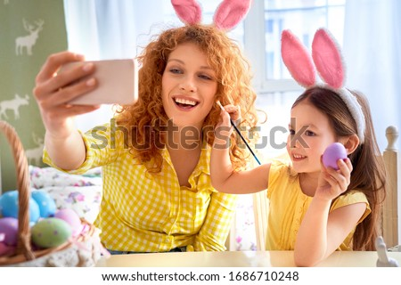 Happy young mother making selfie photo on smartphone while her little child girl holding painting easter egg in hands