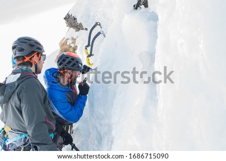 Roumania, Fagaras mountains, february, 2019: Climbers learning how to ice climb at a ice wall #1686715090