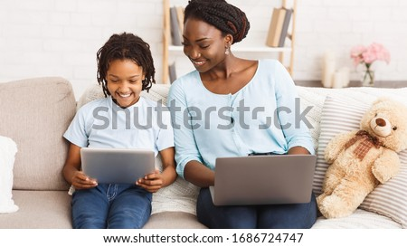 Stay at home african mom working remotely on laptop and helping her child with homework, using tablet and laptop