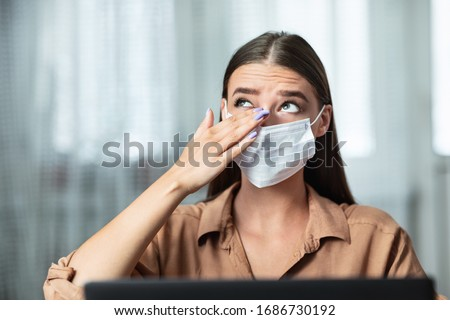 Don't Touch Your Face. Girl wearing surgical mask rubbing her eye with dirty hands, working on laptop #1686730192