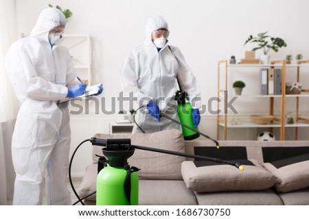 Anti coronavirus disinfection. Men in hazmat suits cleaning home, epidemic, quarantine #1686730750