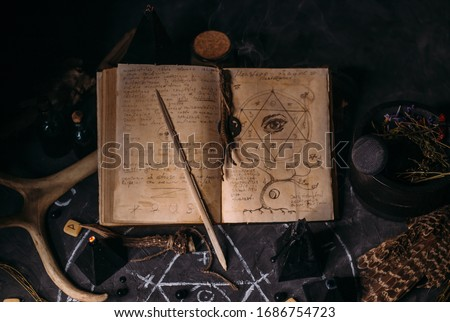 Open old book with magic spells, runes, black candles on witch table. Occult, esoteric, divination and wicca concept. Halloween vintage background Royalty-Free Stock Photo #1686754723