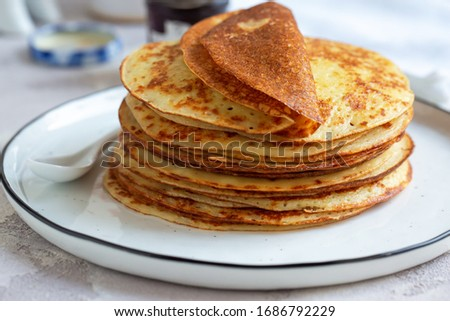 Fresh baked french crepes or Russians blinis on beautiful plate. Royalty-Free Stock Photo #1686792229