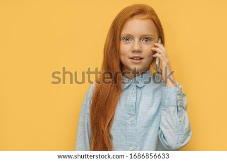 girl talking with friend on phone, isolated over yellow. awesome child with long red hair surprisingly react on news from friend, look at camera. children, people, modern technologies concept