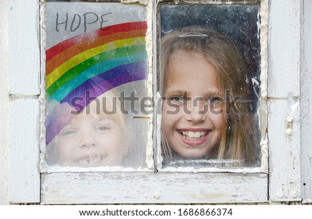 two young girls in grungy window with rainbow sign of hope