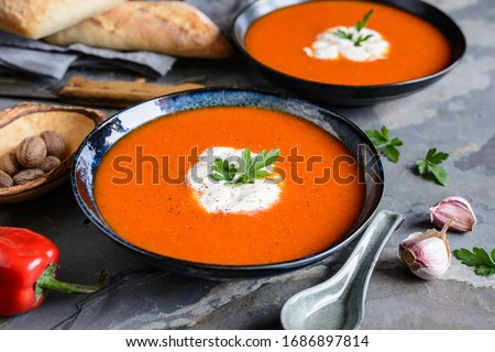 Creamy roasted red bell pepper soup with sour cream in a ceramic plate #1686897814