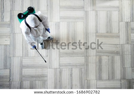 Stop COVID-19. Top view of an unrecognizable person in white chemical protection suit doing disinfection and spraying of public areas to stop highly contagious corona virus. Copy space provided. #1686902782