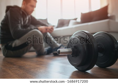 Young ordinary man go in for sport at home. Cut view with blurred background where workout beginner sit on floor and has rest after hard workout. Big dumbbells on floor. Sport amateur #1686917200
