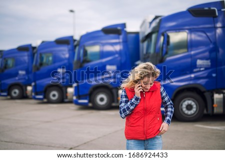 Female trucker talking on the phone about shipment that has to be delivered. Truck vehicles parked in background. #1686924433