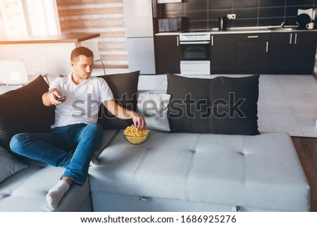 Young man watch tv in his own apartment. Serious concentrated guy hold remote control in hand and get snack from bowl. Watch movie or tv in room alone. Calm peaceful ordinary guy on picture