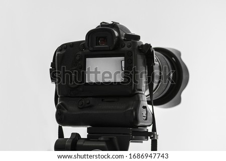 Back of a generic and unbranded black DSLR camera mounted on a tripod in a white studio environment. #1686947743