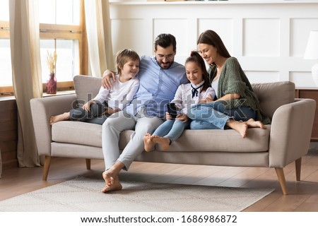 Full length happy young family couple relaxing on comfortable sofa with smiling two little children siblings, using smartphone. Joyful parents spending free weekend time with kids in living room. #1686986872