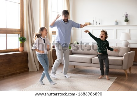 Excited young father enjoying funny family activity with small kids in living room. Energetic little children siblings dancing to favorite pop music with cheerful daddy at free weekend time at home. #1686986890