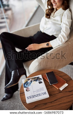 Stylish young woman resting in chair near round desk with business book, smartphone and wallet stock photo