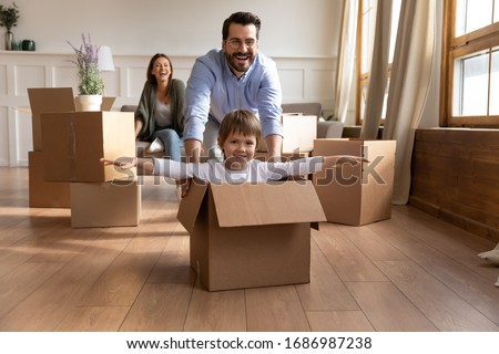 Full length happy young father in glasses pushing carton box with small kid son in new living room. Overjoyed family couple having fun with little child, celebrating moving into flat apartment. #1686987238