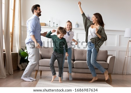 Full length overjoyed married couple dancing to favorite music in living room with adorable two children siblings. Excited happy kids son daughter having fun with energetic young parents at home. #1686987634