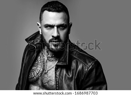 In his brutal style. Brutal hispanic man. Bearded latino man with brutal tattoo on muscular chest. Brutal and athletic, copy space. #1686987703
